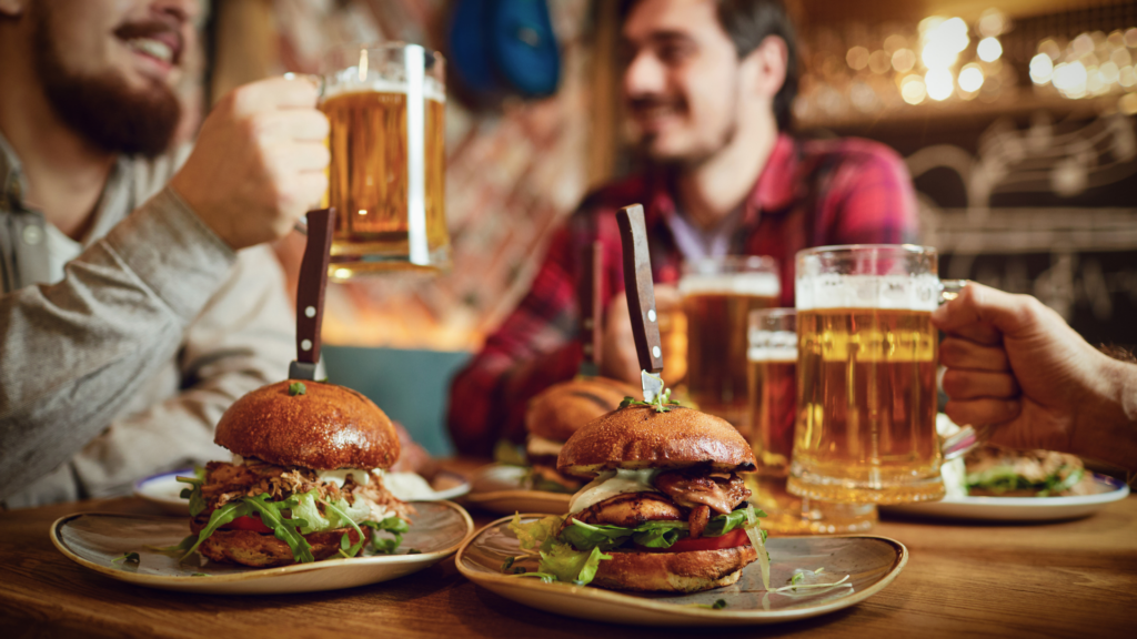 Three men sitting at a pub drinking beer with burgers around them.